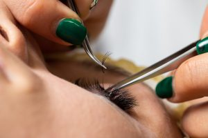 Woman applying eyelash extensions