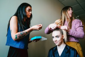 Two women styling another woman's hair and makeup