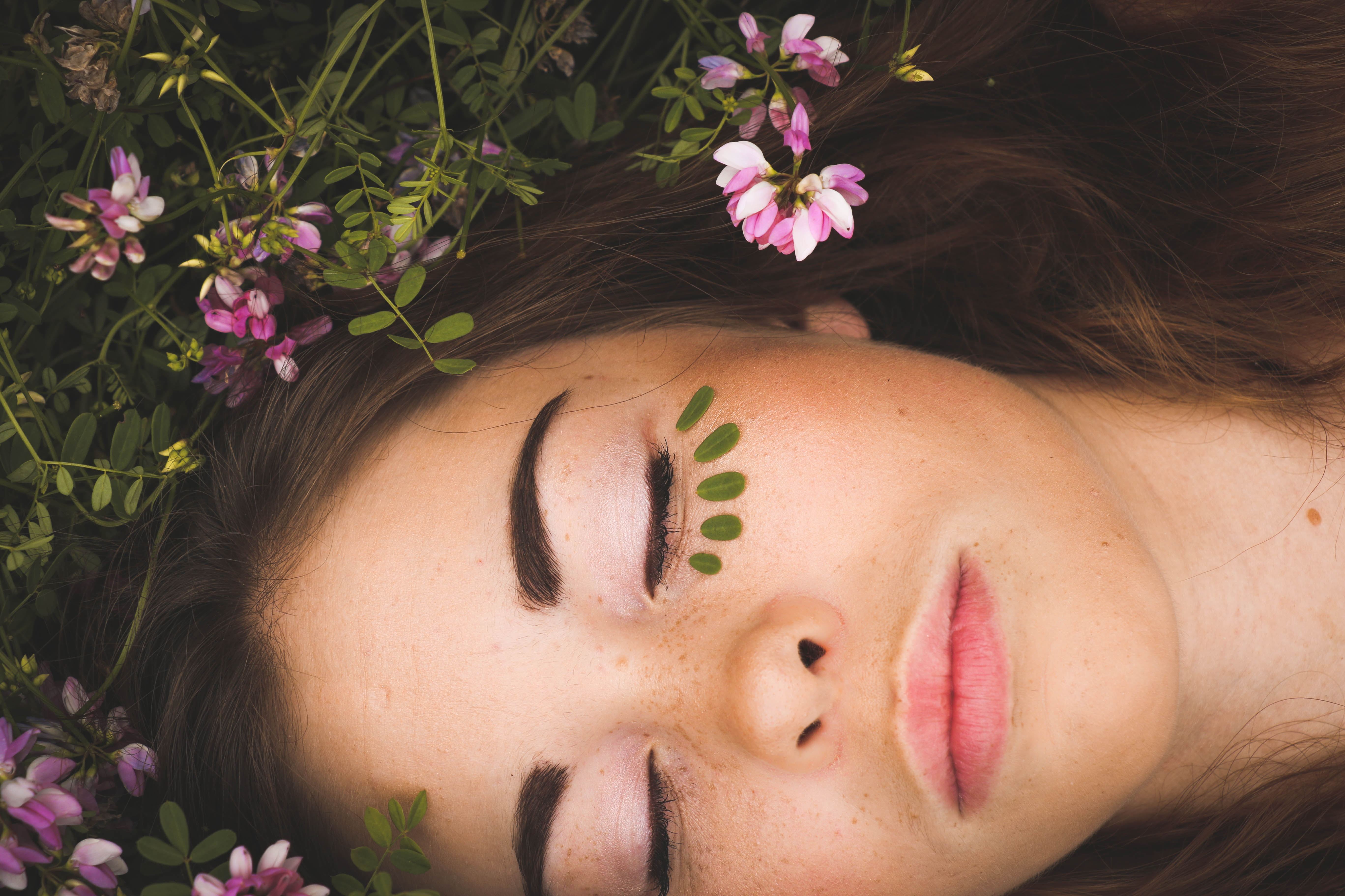 woman laying in grass with lotion on her face